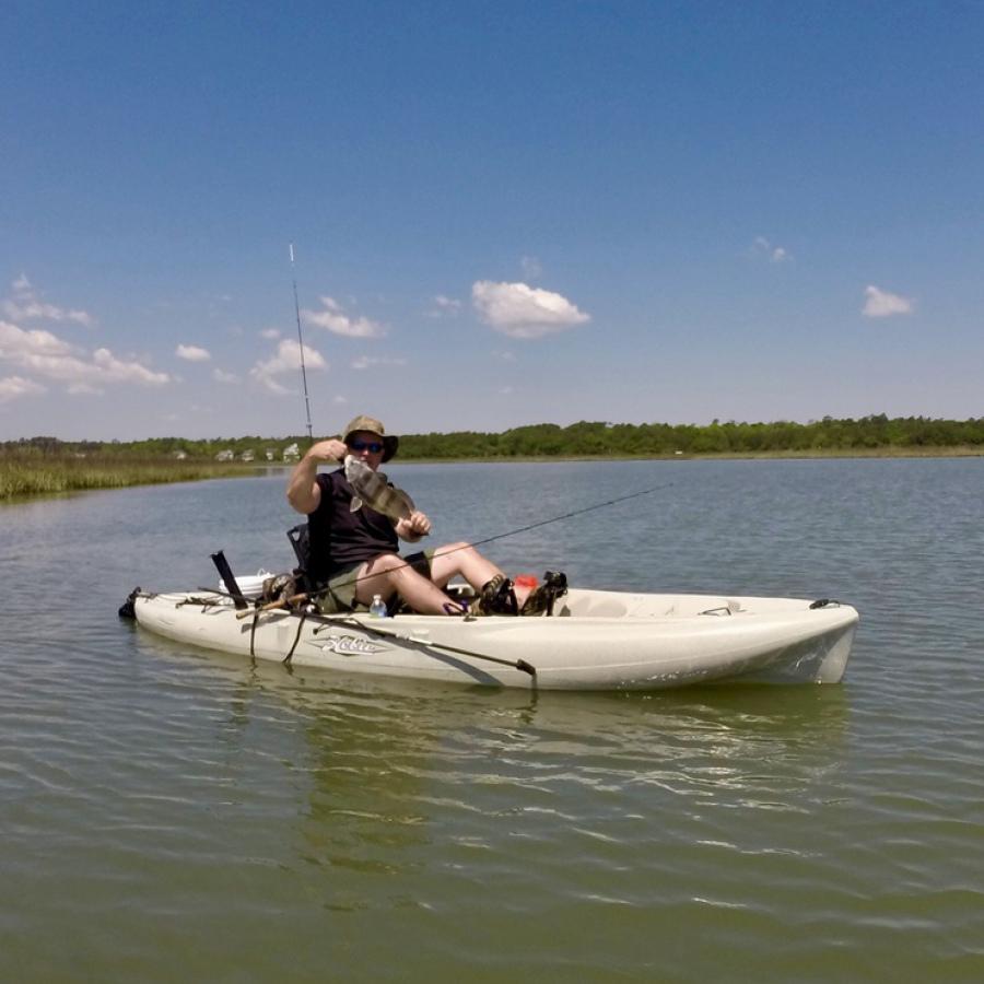 Man kayak fishing in white kayak